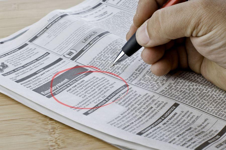 Bezrobotny mężczyzna szukający pracy w gazecie