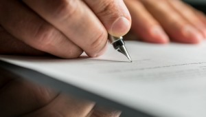 Mężczyzna podpisujący umowę o pracę.